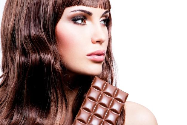 Portret van mooie sexy vrouw met reep chocola - die op wit wordt geïsoleerd.