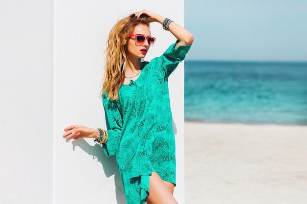 Portret van mooie slanke tan vrouw met perfecte voorspelling in heldere boho strandjurk en coole accessoires