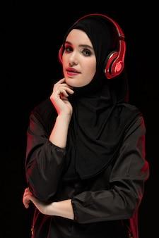 Portret van mooie slimme jonge moslimvrouw die zwarte hijab dragen die aan muziek in hoofdtelefoons luisteren