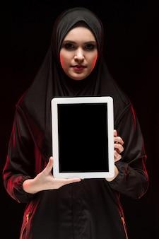 Portret van mooie slimme jonge moslimvrouw die zwarte hijab holdingstablet in haar handen draagt