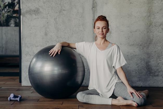 Portret van mooie sportieve roodharige dame zit sierlijk op houten vloer in fitness- of pilatesstudio en lacht gelukkig naar de camera terwijl ze met één hand op fitball naast halters leunt
