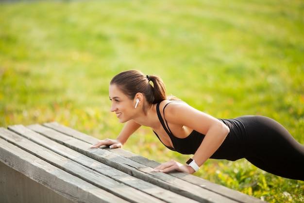 Portret van mooie sportieve vrouw 20s in sportkleding doen push-ups en luisteren naar muziek met bluetooth-oordopjes tijdens training in groen park