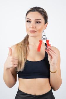 Portret van mooie sportieve vrouw met hand expander duimen opdagen.