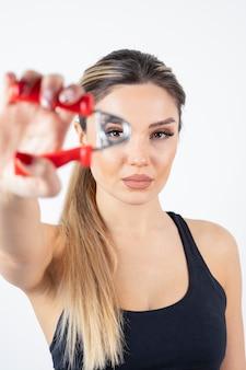 Portret van mooie sportieve vrouw met handexpander.