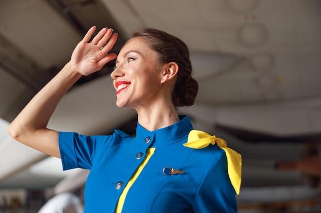 Portret van mooie stewardessen in helderblauw uniform glimlachend terwijl ze wegkijken, staande voor passagiersvliegtuigen. beroep concept