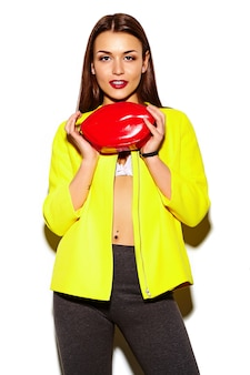 Portret van mooie stijlvolle jonge vrouw in gele jas met rode zak in handen