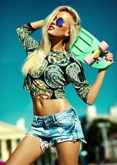 Portret van mooie stijlvolle jonge vrouw met skateboard