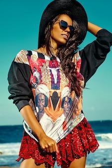 Portret van mooie stijlvolle jonge vrouw op het strand