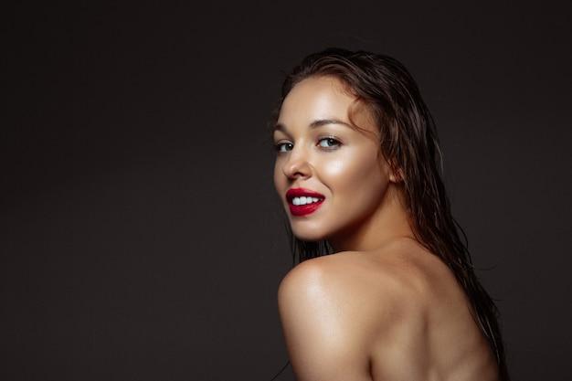 Portret van mooie stijlvolle vrouw geïsoleerd op donkere studio achtergrond