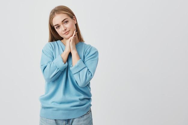 Portret van mooie, tedere, charmante europese vrouw met rechte blonde haren dragen van casual kleding kijken met rustige en doordachte expressie, met haar handen onder haar kin.