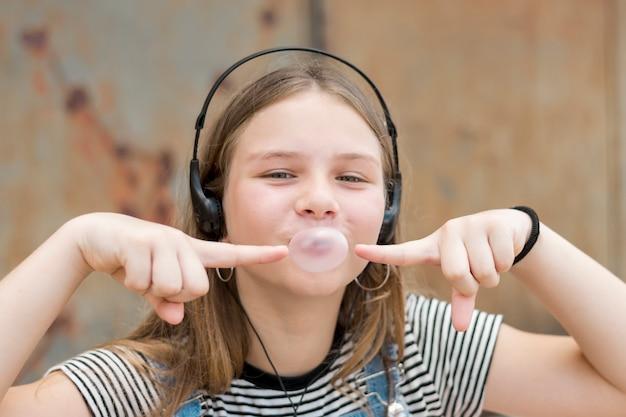 Portret van mooie tiener die hoofdtelefoon draagt die op kauwgomballon richt