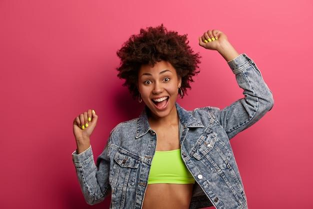 Portret van mooie tienermeisje danst gelukkig, houdt armen omhoog en balde vuisten, geniet van mooie muziek op feestje, draagt top en spijkerjasje, geïsoleerd op roze muur, voelt vrolijk en zorgeloos