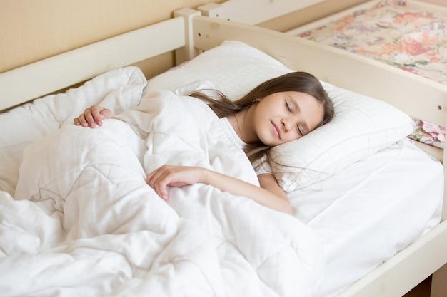 Portret van mooie tienermeisje slapen op wit linnen