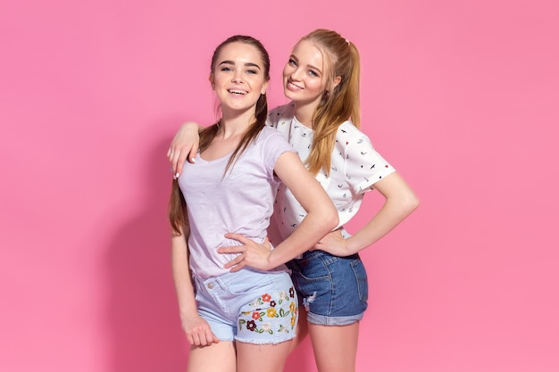 Portret van mooie twee beste vrienden meisjes samen poseren op een roze muur