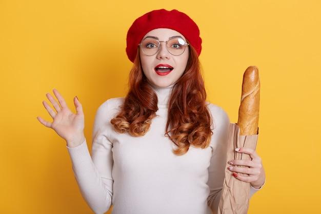 Portret van mooie verbaasde jonge vrouw met papieren zak met brood stokbrood op geel