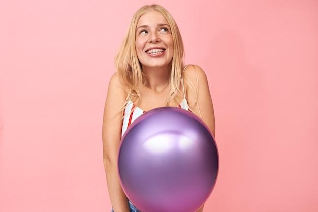 Portret van mooie verlegen tienermeisje met lang steil haar op zoek naar boven met doordachte glimlach, dagdromen poseren geïsoleerd op lege roze kopie ruimte muur