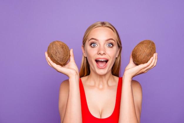Portret van mooie verrukkelijke dame twee kokosnoten in handen houden
