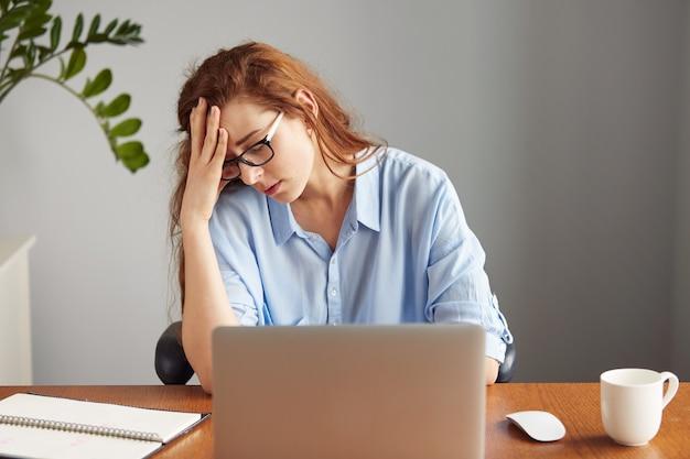Portret van mooie verveelde zakenvrouw, uitgeput op haar elleboog leunend