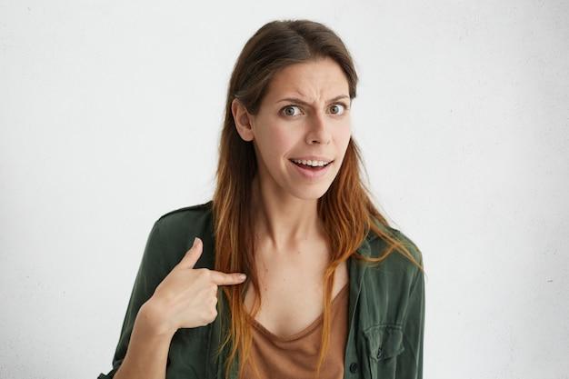 Portret van mooie verwarde vrouw wijzend op zichzelf met wijsvinger. beledigde vrouw die ruzie heeft en met verwondering naar zichzelf kijkt