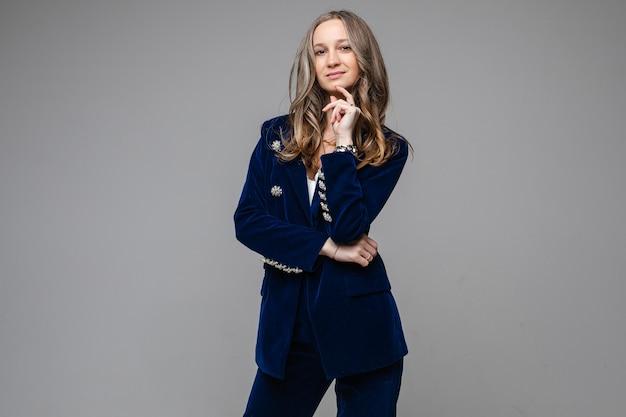 Portret van mooie volwassen vrouw in stijlvol broekpak hand in de buurt van haar kin te houden tijdens het kijken naar camera, op grijs