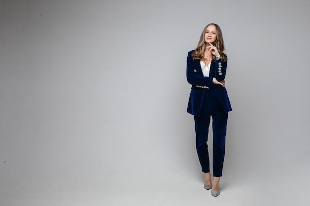 Portret van mooie volwassen vrouw in stijlvol broekpak hand in de buurt van haar kin terwijl kijken naar camera, geïsoleerd op grijze muur