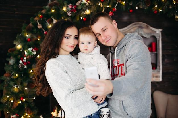 Portret van mooie vrolijke familie in rode hoeden en truien lachen en glimlachen vooraan knuffelen tegen versierde kerstboom