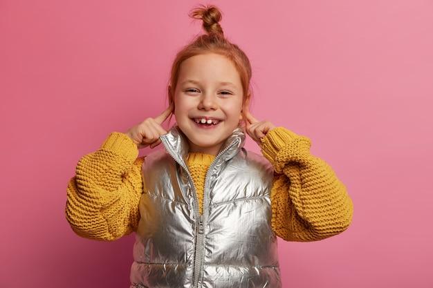 Portret van mooie vrolijke gember meisje plug oren, heeft oprechte glimlach, draagt gebreide trui, vest, poseert tegen roze pastel muur, heeft brede glimlach, vermijdt het luisteren naar luide muziek op feestje