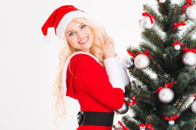 Portret van mooie vrolijke jonge vrouw in de buurt van kerstboom op witte achtergrond