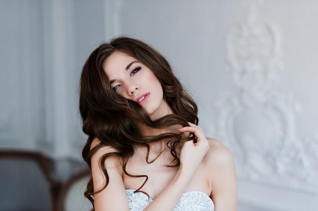 Portret van mooie vrolijke krullend bruid, met vingers in het haar. bruiloft kapsel en make-up.