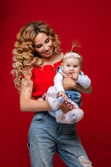 Portret van mooie vrolijke moeder in rode bovenkant en jeans die haar babydochter in wapens koesteren die haar met glimlach op rode achtergrond bekijken. geïsoleerd. studio opname.