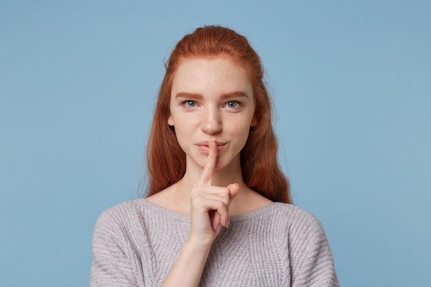 Portret van mooie vrolijke roodharige jonge vrouw toont een gebaar van stilte