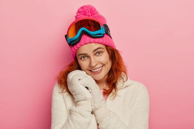 Portret van mooie vrolijke roodharige vrouw draagt zachte wanten, winter witte trui, roze muts met pompon en snowboard bril, glimlacht teder, geïsoleerd op roze achtergrond.
