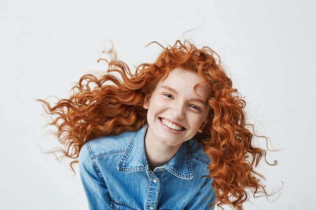 Portret van mooie vrolijke roodharige vrouw met vliegende krullend haar lachend lachen.