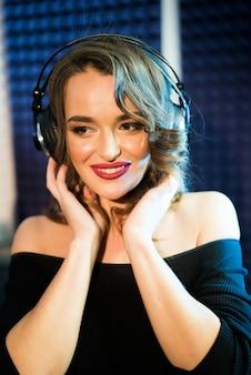 Portret van mooie vrolijke vrouw die met blote schouders aan muziek op hoofdtelefoons luistert