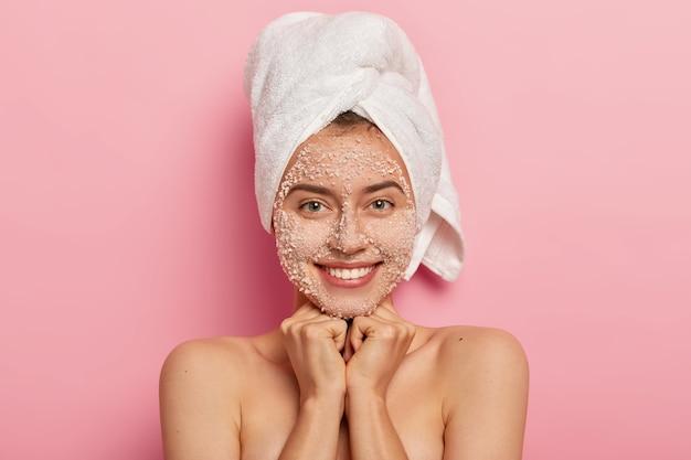 Portret van mooie vrolijke vrouw glimlacht zachtjes, geniet van zachtheid van de huid na schoonheidsprocedures, lacht aangenaam, toont witte tanden, heeft schattige blik op camera, vormt tegen roze achtergrond