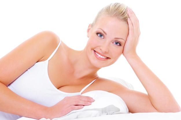 Portret van mooie vrolijke vrouw met gelukkige brede glimlach die op het witte bed ligt