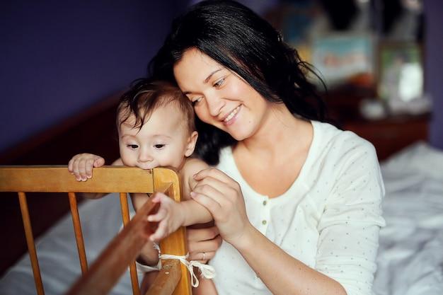 Portret van mooie vrolijke vrouw met haar schattige baby plezier samen thuis. lieve naakte jongen en brunette moeder.