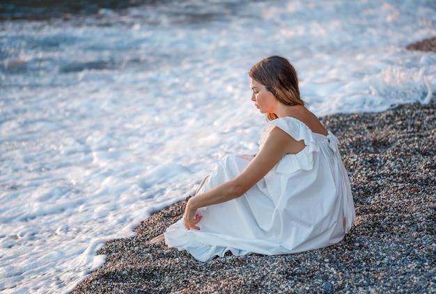 Portret van mooie vrouw bij kust die alleen en in witte kleding zitten denken en droevig kijken