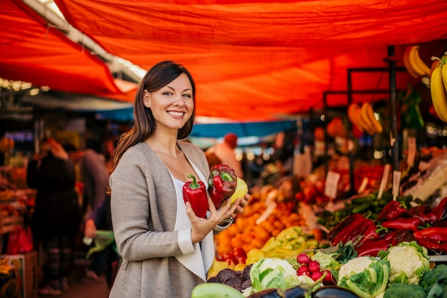 Portret van mooie vrouw bij landbouwersmarkt het kopen paprika.
