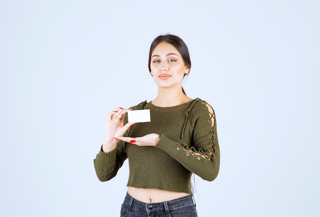 Portret van mooie vrouw die blanco visitekaartje toont.