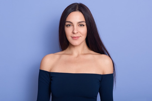 Portret van mooie vrouw die camera met charmante glimlach bekijkt, gelukkig meisje dat donkerblauwe kleding met naakte schouders draagt