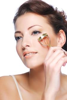 Portret van mooie vrouw die curl wimpers maakt met behulp van curling cosmetisch hulpmiddel