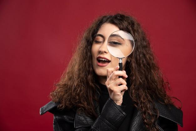 Portret van mooie vrouw die door vergrootglas kijkt.