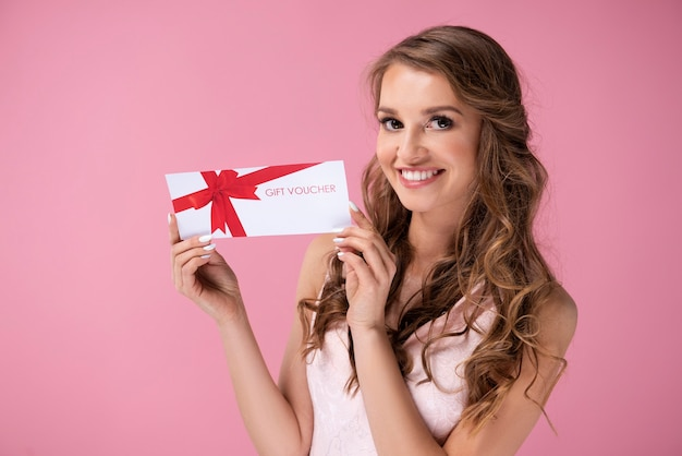 Portret van mooie vrouw die een cadeaubon geeft