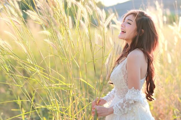 Portret van mooie vrouw die een gelukkige tijd hebben en onder grasgebied genieten van in aard