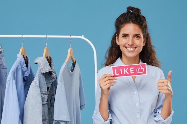 Portret van mooie vrouw die en duim met kleren op het rek op de achtergrond glimlacht toont