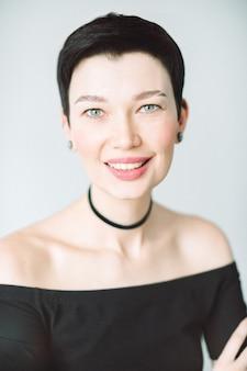 Portret van mooie vrouw die en in zwarte kleding kijkt glimlacht