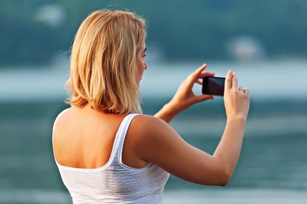 Portret van mooie vrouw die foto's met mobiele telefoon neemt.