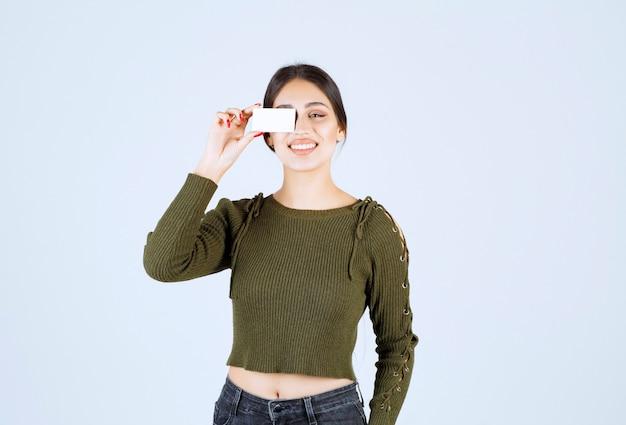 Portret van mooie vrouw die gelukkig blanco visitekaartje toont.