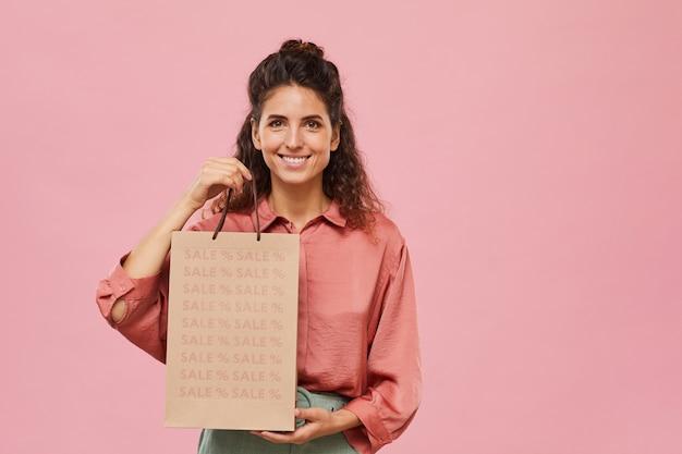 Portret van mooie vrouw die het winkelen in de uitverkoop doet die zij papieren zak houdt en glimlacht